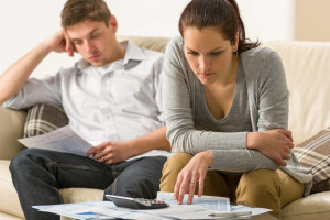 Annoyed couple calculating their finances during recession