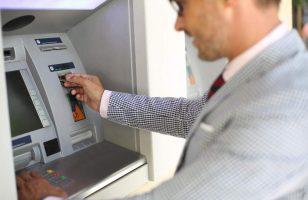 człowiek wypłacający pieniądze z bankomatu
