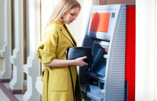 kobieta wypłacająca pieniądze z bankomatu