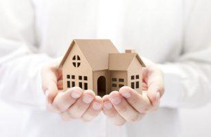 model domu w dłoniach kobiety