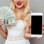 kobieta z telefonem i plikiem banknotów