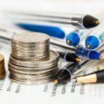 pieniądze i długopisy na biurku