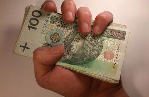 dłoń ściskająca garść banknotów 100 zł