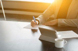kobieta podpisująca dokument przy biurku