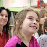 grupa uśmiechniętych dzieci i pani przedszkolanka