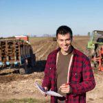 rolnik z dokumentami w dłoni a w tle pole i maszyny rolnicze