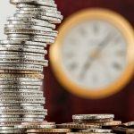 stos monet ułożonych na sobie i zegar na ścianie w tle