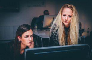 dwie kobiety w biurze patrzą na ekran komputera