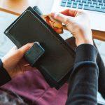osoba sięgająca po kartę kredytową z portfela