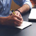 mężczyzna, który pisze coś na kartce