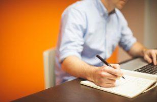 mężczyzna przy biurku pisze coś na kartce papieru