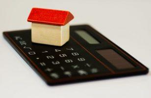 mały drewniany domek na kalkulatorze