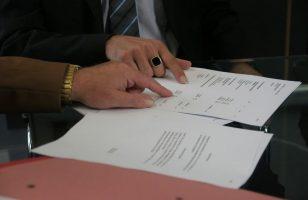 dwie osoby wskazujące palcem na wybrane fragmenty umowy