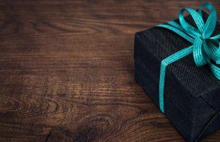 zapakowany prezent na drewnianym blacie