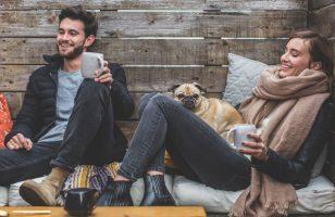 dwoje ludzi z psem odpoczywa w pozycji siedzącej