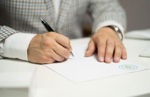 mężczyzna podpisujący dokument długopisem