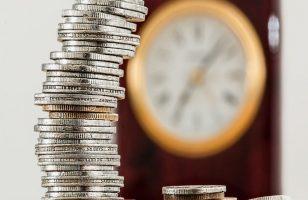 zegar i stos ułożonych monet