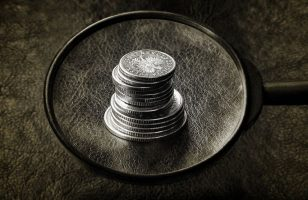 srebrne monety pod lupą