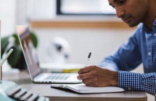 mężczyzna pracujący przy laptopie pisze coś na kartce