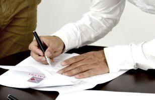 ludzie podpisujący dokument