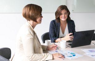 dwie kobiety siedzące w biurze