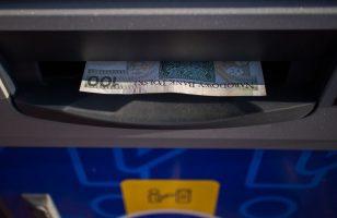 banknot 100 zł podczas transakcji w bankomacie