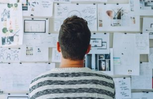 mężczyzna spogląda na tablicę z zadaniami