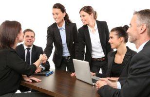 uśmiechnięci ludzie w biurze podczas podpisywania umowy