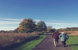 para starszych ludzi idzie wzdłuż ulicy pod rękę