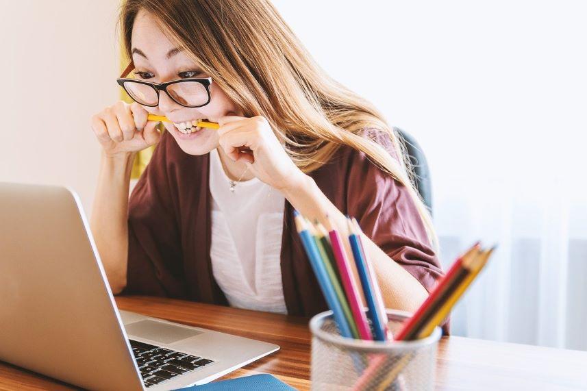 kobieta gryząca długopis na widok czegoś w laptopie
